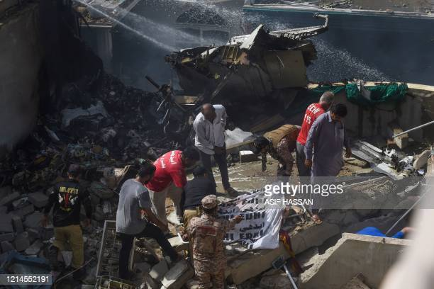 Graphic content / Rescue workers cover the body of a victim they recovered from the rubbles after a Pakistan International Airlines flight crashed in...