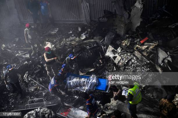 Graphic content / Rescue workers move a body of a victim from the wreckage after a Pakistan International Airlines aircraft crashed at a residential...
