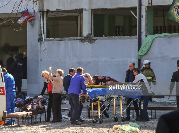 Graphic content / Rescuers carry an injured victim of a blast at at a college in the city of Kerch on October 17 2018 Thirteen people were killed and...