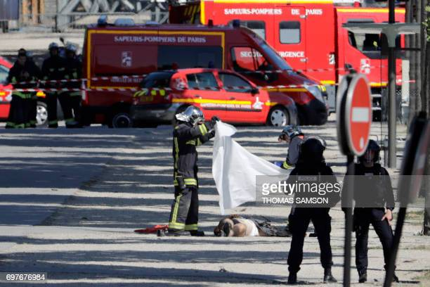 Graphic content / Rescuers cover with a white sheet the body of a suspect lying in a sealed off area of the ChampsElysees avenue in Paris on June 19...