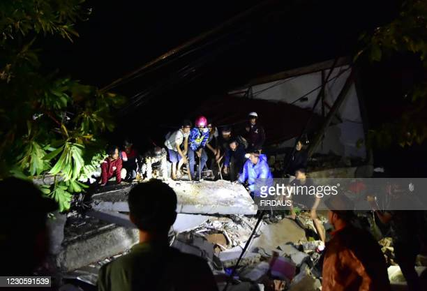 Graphic content / Rescuers search for survivors at a collapsed building in Mamuju city on January 15 after a 6.2-magnitude earthquake rocked...