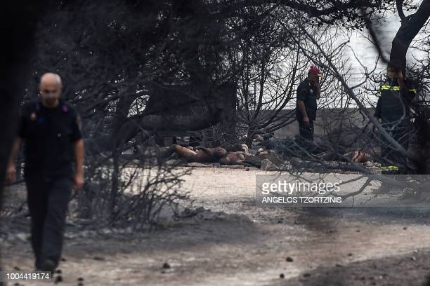 Graphic content / Rescuers stand near dead people following a wildfire at the village of Mati near Athens on July 24 2018 Fifty people have died and...