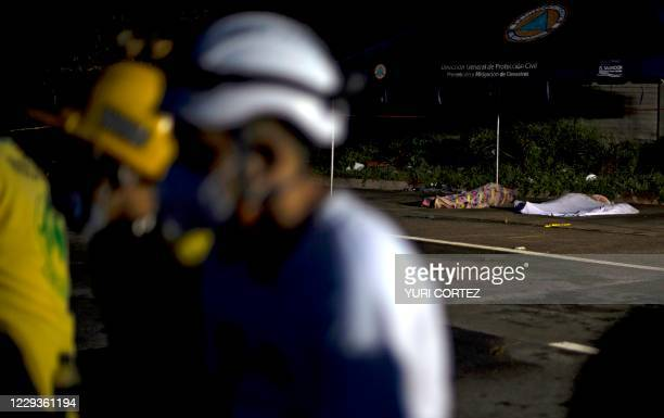 Graphic content / Rescuers take a break near the bodies of two victims of a landslide in Nejapa, El Salvador on October 30, 2020. - A landslide...