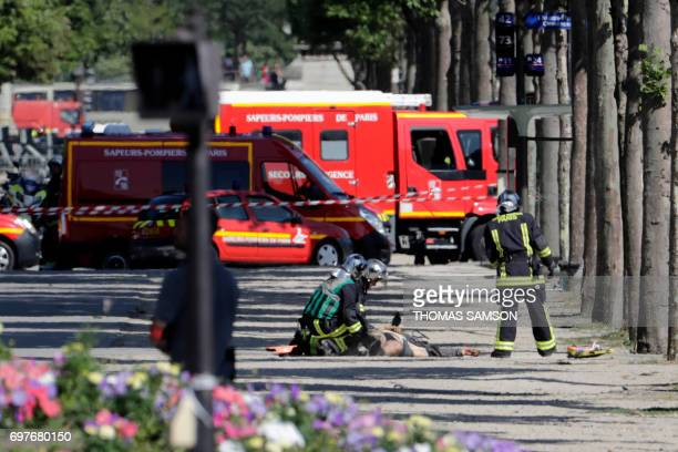 Graphic content / Rescuers tend to the body of a suspect lying in a sealed off area of the ChampsElysees avenue in Paris on June 19 after a car...