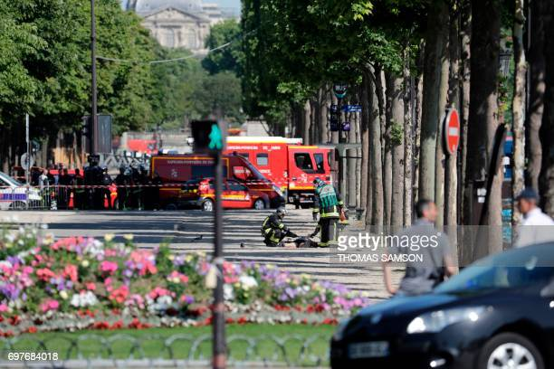 Graphic content / Rescuers tend to the body of the suspect lying in a sealed off area of the ChampsElysees avenue in Paris on June 19 after a car...
