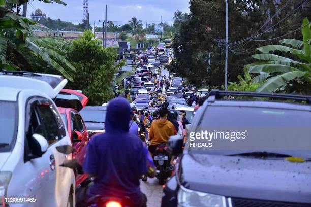Graphic content / Residents crowd a road as they attempt to leave Mamuju on January 15 after a 6.2-magnitude earthquake rocked Indonesia's Sulawesi...
