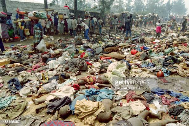 Rwandan refugees pass on July 18 1994 by the corpses of over hundred compatriots who were trampled in the eastern Zairean border town of Goma on July...