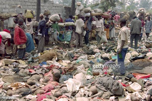 Rwandan refugees scavenge clothes on July 18 1994 from some of the corpses of compatriots who were crushed to death in the eastern Zairean border...