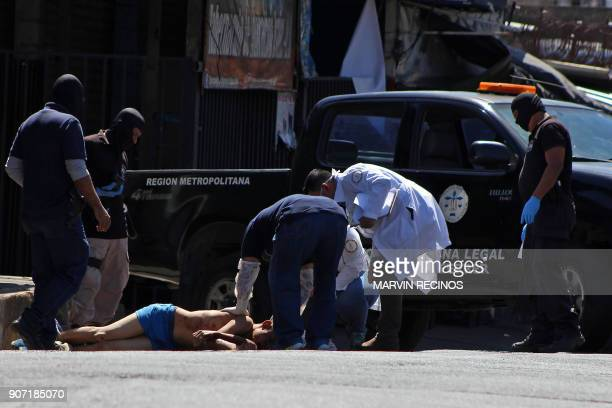 Graphic content / Salvadoran forensic police works at a crime scene where the body of a young man allegedly murdered by gang members lies on the...