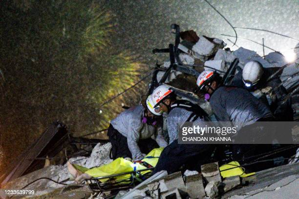 Graphic content / Search and Rescue personnel pull a body out of the rubble after the partial collapse of the Champlain Towers South in Surfside,...
