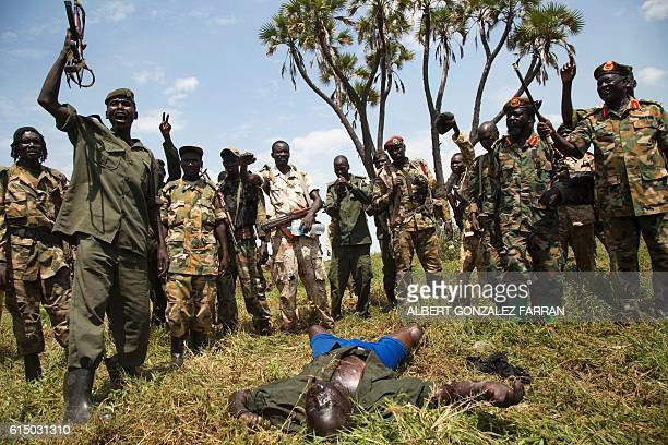 Graphic content / Soldiers of the Sudan People Liberation Army celebrate their victory over the body of a dead rebel soldier in Lelo outside Malakal...