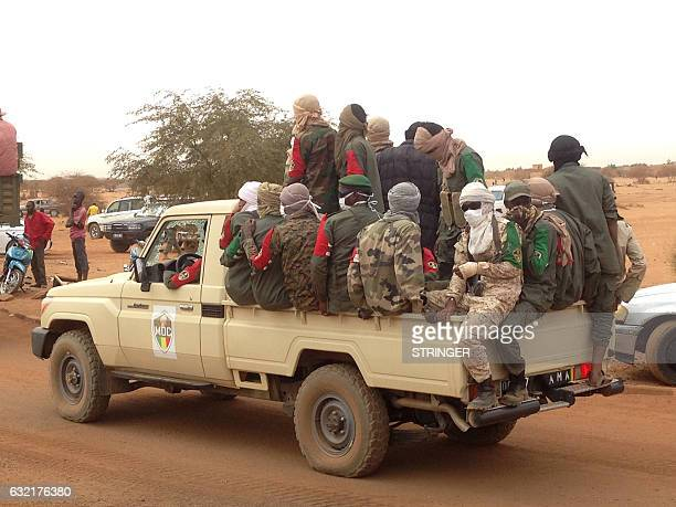 Graphic content / Soldiers stand aboard a pickup truck following a suicide bomb attack that ripped through a camp grouping former rebels and...