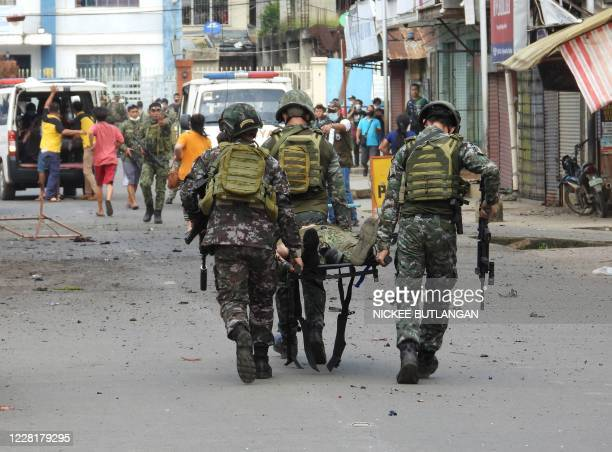 Graphic content / Soldiers stretcher away a comrade after an improvised bomb exploded next to a military vehicle in the town of Jolo on Sulu island...