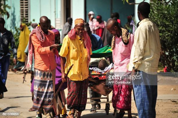 Graphic content / Somali men carry in a stretcher a man injured in the explosion of a truck bomb in the centre of Mogadishu on October 15 2017 A...