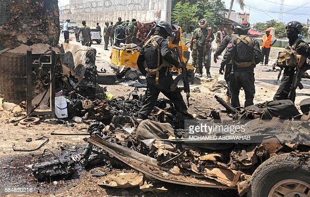 Graphic content / Somali security investigate the scene of a suicide attack in Mogadishu on July 31 2016 Six people were killed in a gun and carbomb...
