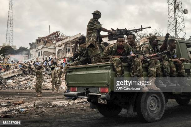Graphic content / Somali soldiers patrol on the scene of the explosion of a truck bomb in the centre of Mogadishu on October 15 2017 A truck bomb...