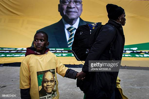 Graphic content / South African ruling party African National Congress supporters walk in front of a Jacob Zuma flag during the final Municipal...