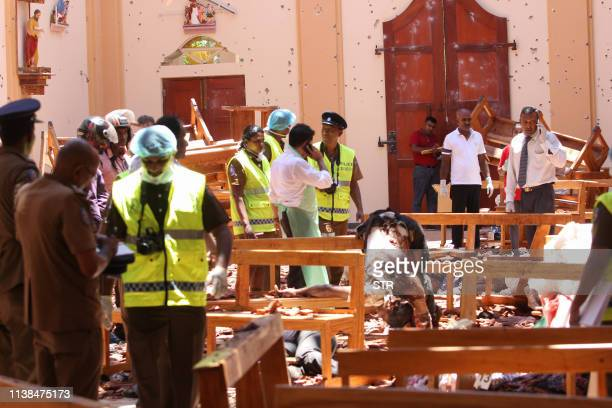 Graphic content / Sri Lankan security personnel walk past debris next to a dead body slumped over a bench following an explosion in St Sebastian's...