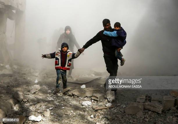 Graphic content / Syrian civilians flee from reported regime air strikes in the rebelheld town of Jisreen in the besieged Eastern Ghouta region on...