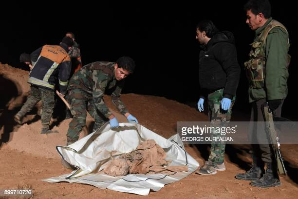 Graphic content / Syrian forces excavate a site said to be a mass grave by state news agency SANA west of Raqa province on December 29 2017 Two mass...