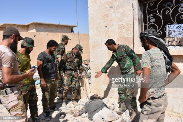 Graphic content / Syrian progovernment members stand next to a body in the Jamiyet alRuwad neighbourhood on the northern outskirts of Deir Ezzor on...