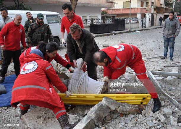 Graphic content / Syrian Red Crescent personnel evacuate the body of a man following a reported mortar strike by rebel fighters in a governmentheld...