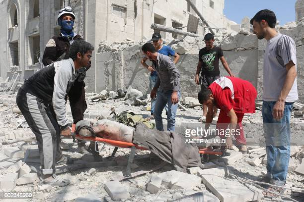 Graphic content / Syrian rescue workers and volunteers carry a body following a reported air strike on the rebelheld Salihin neighbourhood of the...