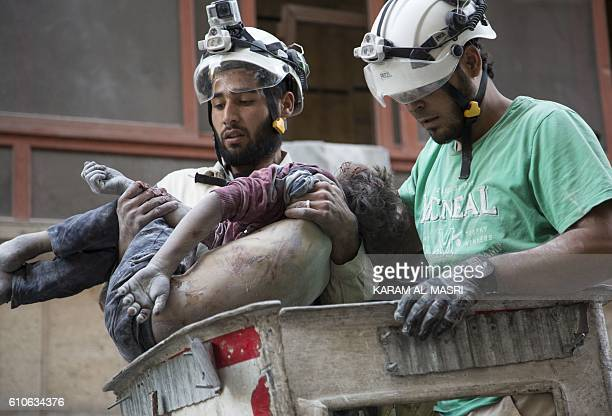 Graphic content / Syrian rescuers hold the body of a girl after pulling it from rubble of a budling following government forces air strikes in the...