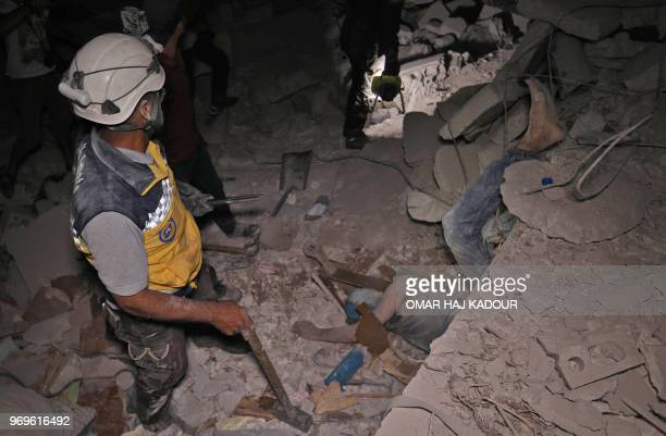 Graphic content / Syrian rescuers known as White Helmets recover bodies in Zardana in the mostly rebelheld northern Syrian Idlib province following...