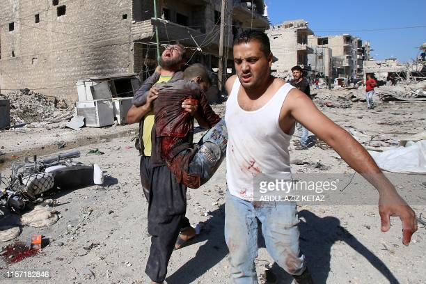 Graphic content / Syrians carry a badly wounded victim amid the rubbble following a reported Russian air strike on July 22, 2019 on Maaret al-Numan...