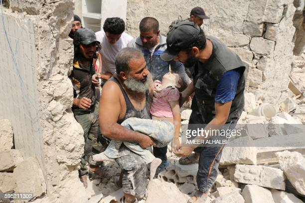 Graphic content / Syrians carry a wounded child in the rubble of buildings following a barrel bomb attack on the Bab alNairab neighbourhood of the...