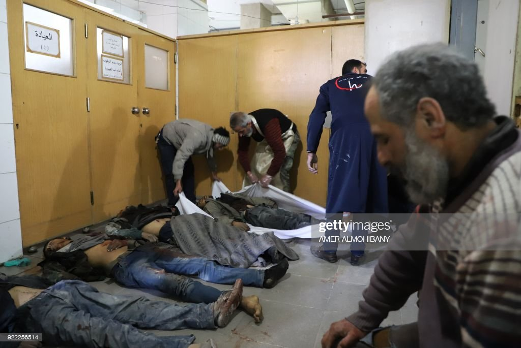 Graphic content / Syrians cover the bodies of people killed in government bombardments at a make-shift hospital in Kafr Batna in the besieged Eastern Ghouta region on the outskirts of the capital Damascus on February 21, 2018. Syrian jets carried out more deadly raids on Eastern Ghouta as Western powers and aid agencies voiced alarm over the mounting death toll and spiralling humanitarian catastrophe. PHOTO / Amer ALMOHIBANY
