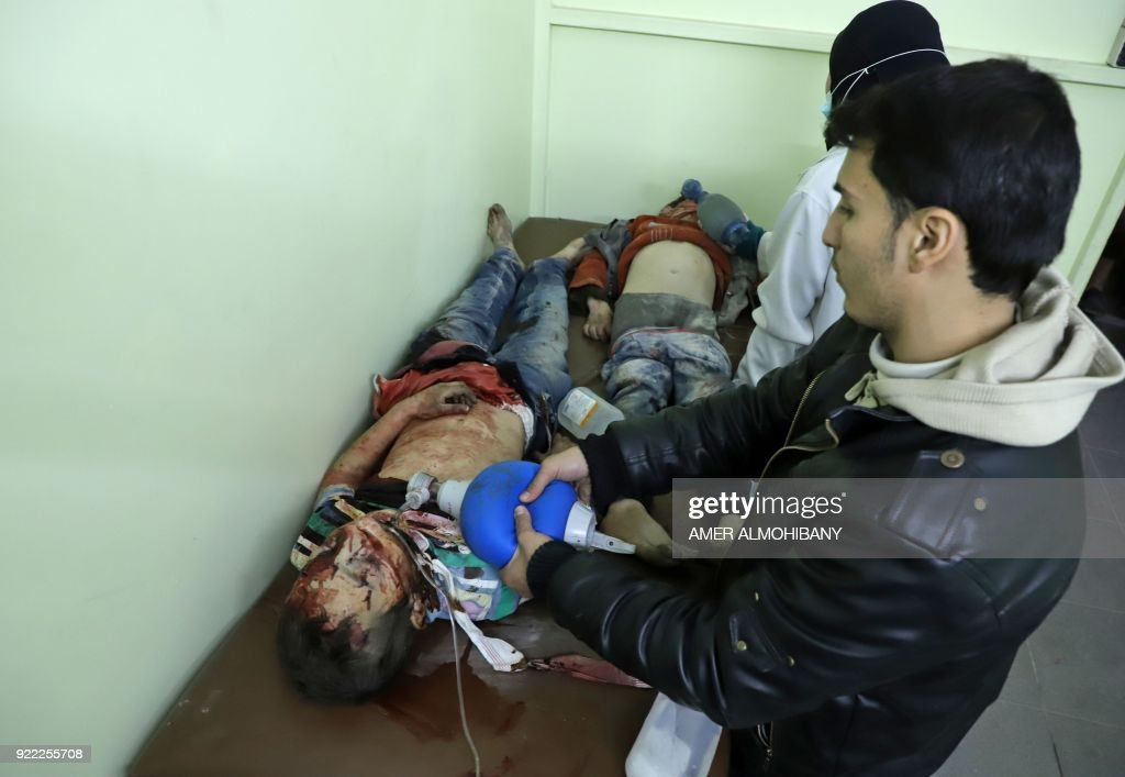 Graphic content / Syrians try to keep young children alive as they wait to receive treatment at a make-shift hospital in Kafr Batna in the besieged Eastern Ghouta region on the outskirts of the capital Damascus following Syrian government bombardments on February 21, 2018. Syrian jets carried out more deadly raids on Eastern Ghouta as Western powers and aid agencies voiced alarm over the mounting death toll and spiralling humanitarian catastrophe. PHOTO / Amer ALMOHIBANY