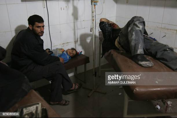 Graphic content / Syrians wounded in reported regime air strikes on the rebelheld enclave of Eastern Ghouta receive treatment at a makeshift hospital...