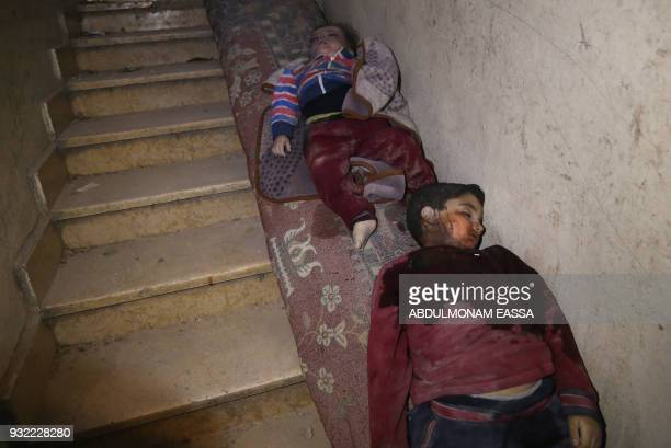Graphic content / The bodies of two Syrian children lie on a rolled carpet in the stairway at the entrance of their building in the rebelheld town of...