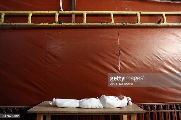 Graphic content / The body of a child is seen at a makeshift morgue following a cluster bomb attack on the rebelheld town of Douma east of the Syrian...