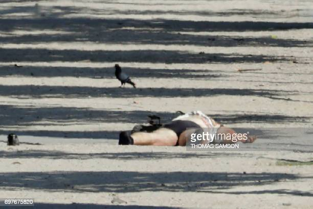 Graphic content / The body of a suspect lying in a sealed off area of the ChampsElysees avenue in Paris is pictured on June 19 after a car crashed...