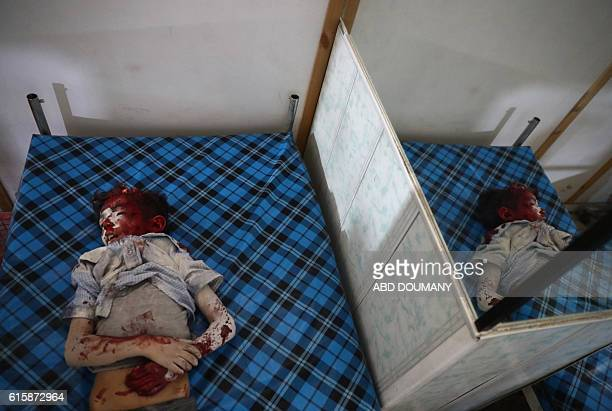 Graphic content / The body of a Syrian boy lies at a makeshift hospital in the rebelheld town of Douma east of the Syrian capital Damascus following...