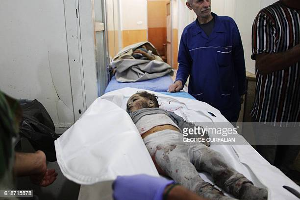 Graphic content / The body of a Syrian child lies on a stretcher at a hospital following rebel rocket attacks in the Shahba neighbourhood of the...