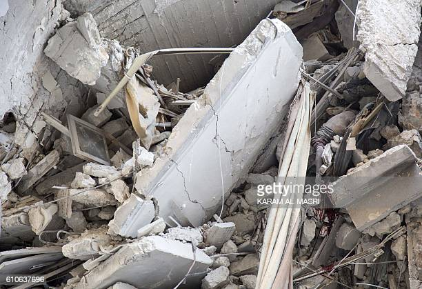 Graphic content / The body of a Syrian girl is seen trapped in the rubble of a building following government forces air strikes in the rebel held...