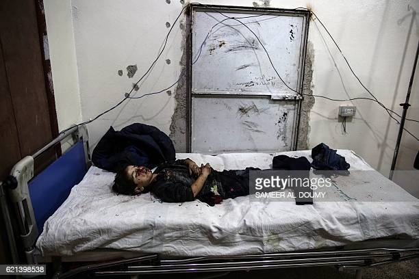 Graphic content / The body of a Syrian girl lies on a bed at a makeshift hospital following reported shelling on a kindergarten in the rebelheld area...