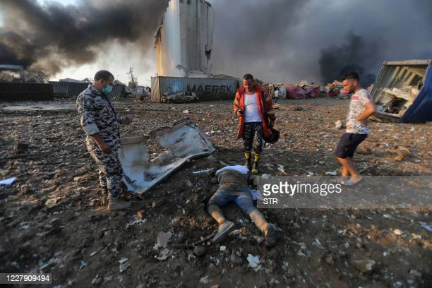 Graphic content / The body of a victim lies at the scene of an explosion at the port in Beirut on August 4, 2020. - Two huge explosion rocked the...