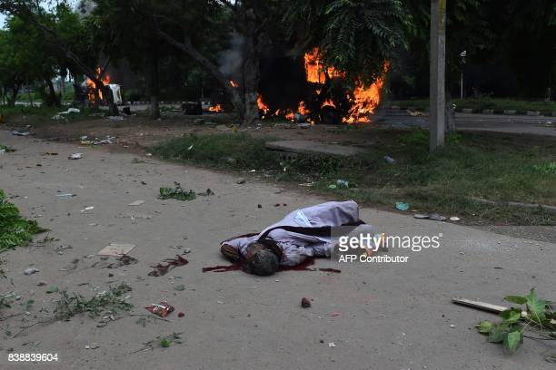 Graphic content / The dead body of a follower of Indian religious leader Gurmeet Ram Rahim Singh lays on the street next to burning vehicles...