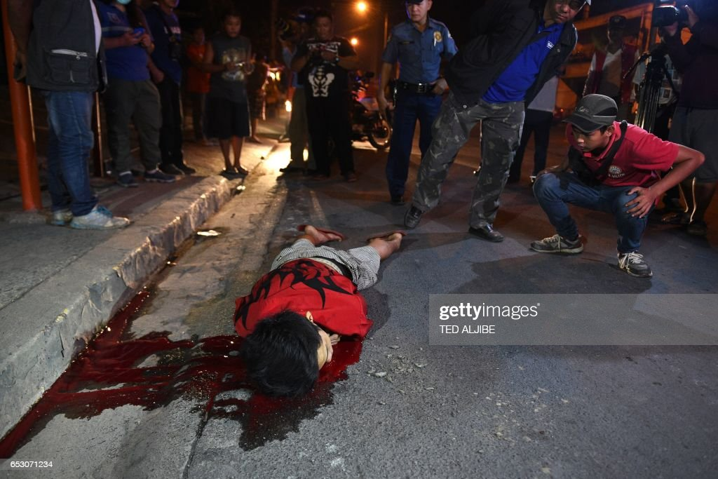 Graphic content / This photo taken March 9, 2017 shows a policeman (R) and members of a village standing over a body, who according to witnesses was thrown from a car and then shot several times by suspects, along a road in Quezon City in suburban Manila. While President Rodrigo Duterte's unprecedented crackdown has claimed the lives of 7,000 people, the impacts on their families are the largely untold stories in what rights groups have called a 'war on the poor'. Amnesty International said in a February report that the killings were overwhelmingly in poor urban areas, with the slain often male breadwinners. MACARAIG