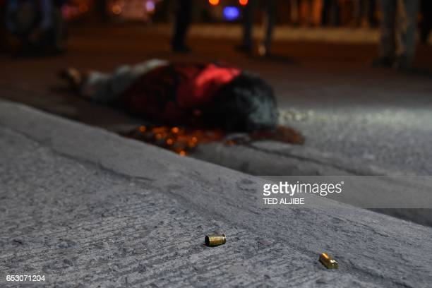 Graphic content / This photo taken March 9 2017 shows empty bullet casings next to a body who according to witnesses was thrown from a car and then...