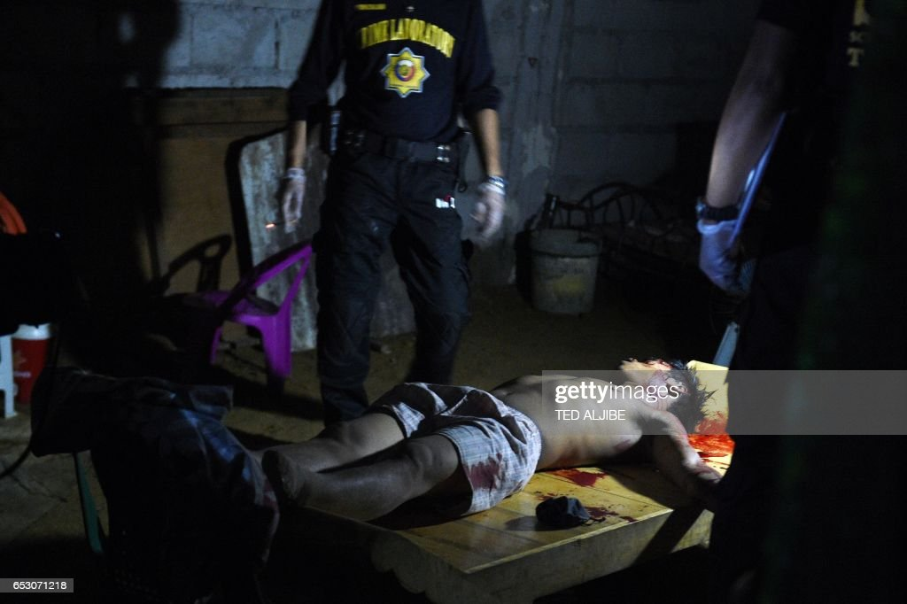 Graphic content / This photo taken March 9, 2017 shows members of the police Scene of the Crime Operatives (SOCO) standing next to the body of resident, a suspected drug user who was allegedly shot by masked men inside his house, near the landfill in Payatas, Quezon City in suburban Manila. While President Rodrigo Duterte's unprecedented crackdown has claimed the lives of 7,000 people, the impacts on their families are the largely untold stories in what rights groups have called a 'war on the poor'. Amnesty International said in a February report that the killings were overwhelmingly in poor urban areas, with the slain often male breadwinners. MACARAIG