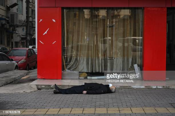 Graphic content / This photo taken on January 30, 2020 shows an elderly man wearing a facemask lying on the pavement after he collapsed and died...