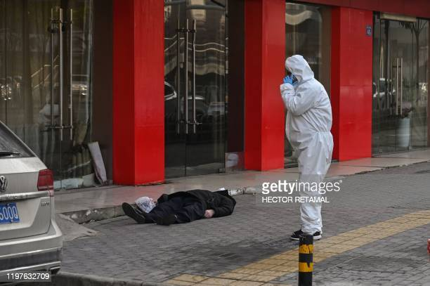 Graphic content / This photo taken on January 30, 2020 shows an official in a protective suit checking on an elderly man wearing a facemask who...