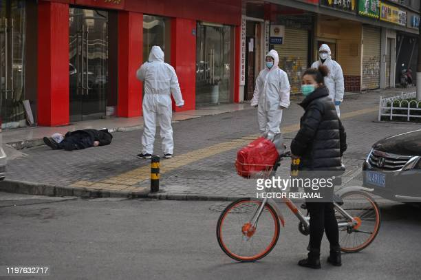 Graphic content / This photo taken on January 30, 2020 shows officials in protective suits checking on an elderly man wearing a facemask who...