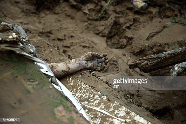 Graphic content / This photo taken on July 10 2016 shows a hand of a victim on the ground in the aftermath of a tropical storm in Bandong town in...